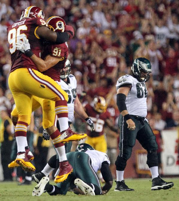 Washington Redskins linebacker Ryan Kerrigan (91) and defensive tackle Barry Cofield celebrate Kerrigan's sack on Philadelphia Eagles quarterback Michael Vick during an NFL football game, Monday, Sept. 9, 2013, in Landover, Md