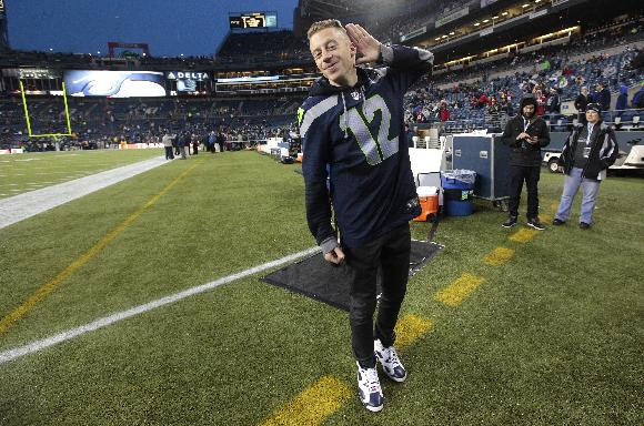 Seattle rap singer Macklemore responds to the crowd at CenturyLink Field prior to an NFL football game between the Seattle Seahawks and the San Francisco 49ers, Sunday, Dec. 23, 2012, in Seattle