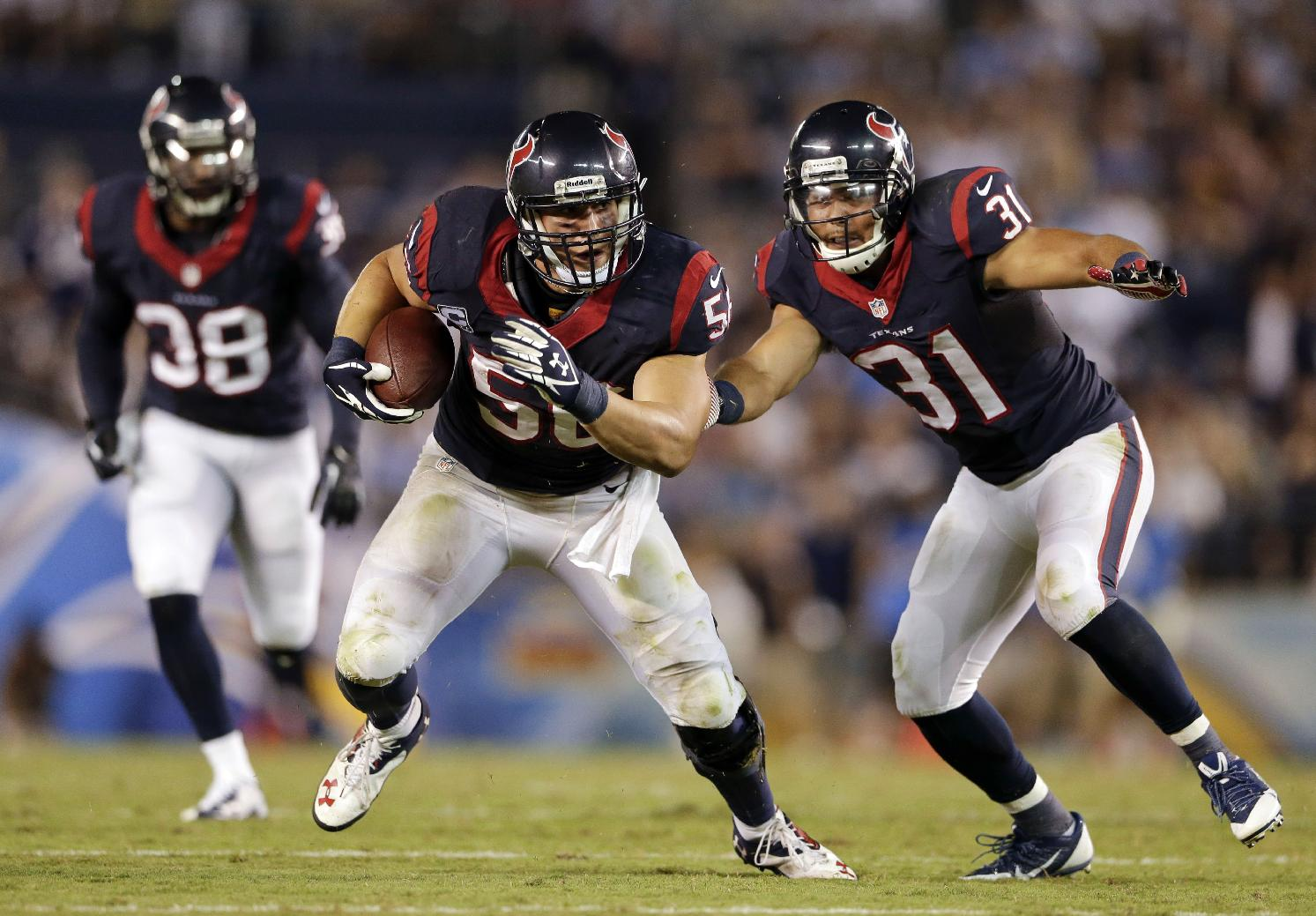 FILE- In this Sept. 9, 2013, file photo, Houston Texans inside linebacker Brian Cushing, center, returns an interception for a touchdown during the second half of an NFL football game against the San Diego Chargers in San Diego. Cushing didn't need long to show he was back after season-ending knee surgery. The linebacker returned an interception for a touchdown, rallying the Texans in their opener