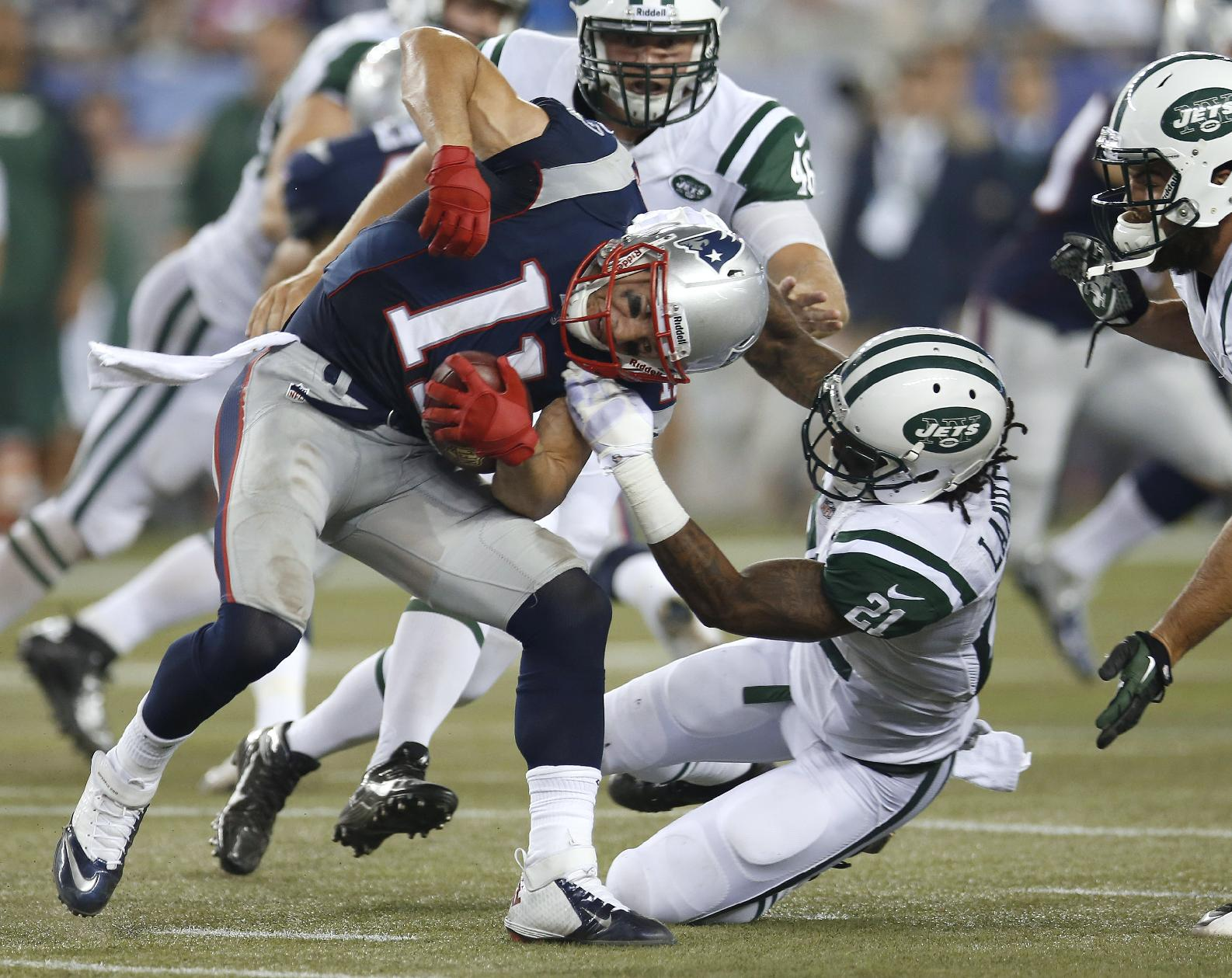 New York Jets defensive back Ellis Lankster (21) tries to tackle New England Patriots wide receiver Julian Edelman (11) during the second quarter of an NFL football game Thursday, Sept. 12, 2013, in Foxborough, Mass