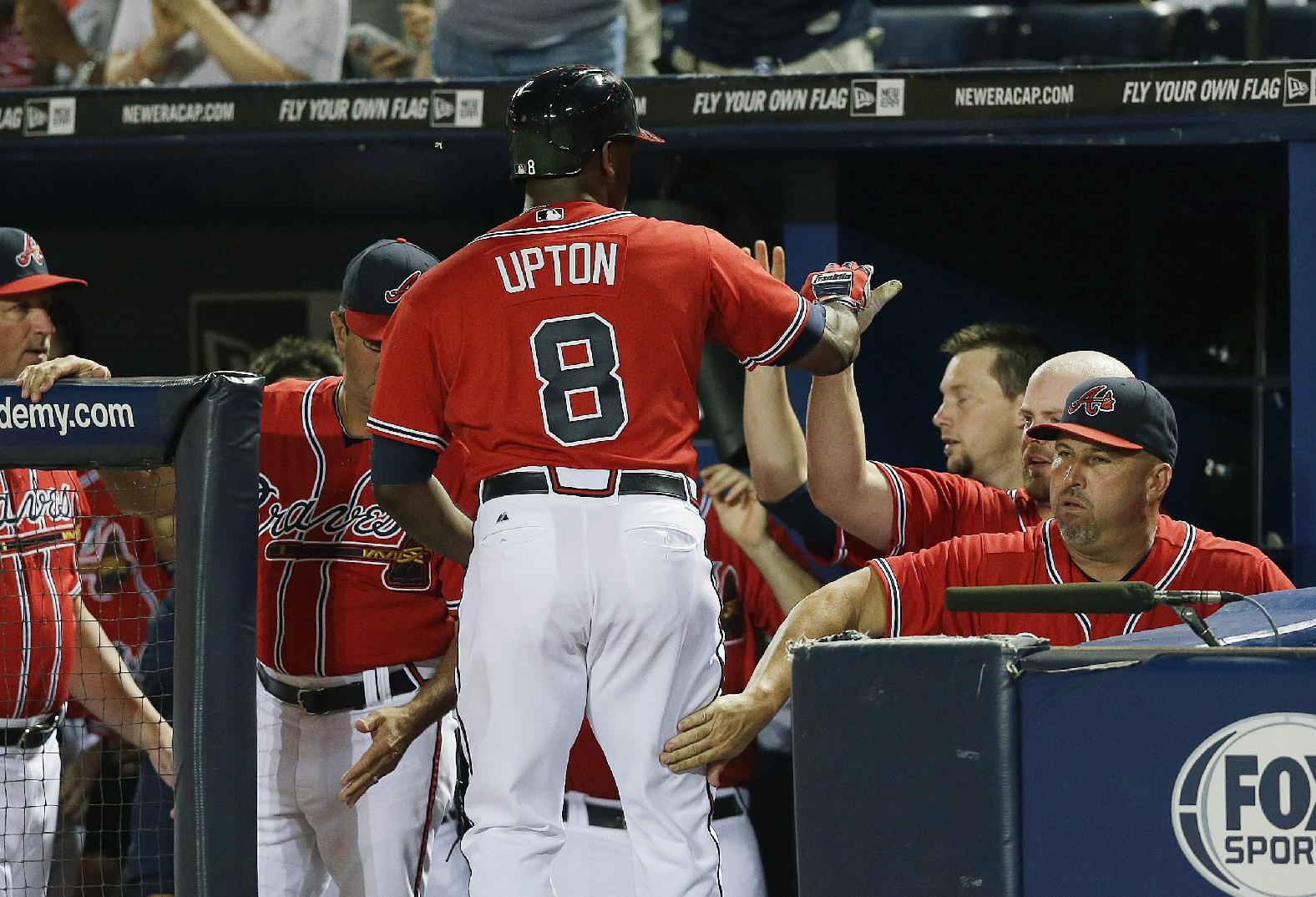 Atlanta Braves' Justin Upton (8) gets a pat on the leg from manager Fredi Gonzalez, right, after hitting a home run in the fourth inning of a baseball game against the San Diego Padres in Atlanta, Friday, Sept. 13, 2013