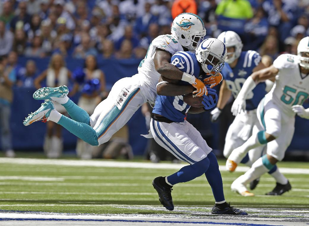 Indianapolis Colts' Reggie Wayne (87) is tackled by Miami Dolphins' Reshad Jones (20) during the first half an NFL football game Sunday, Sept. 15, 2013, in Indianapolis