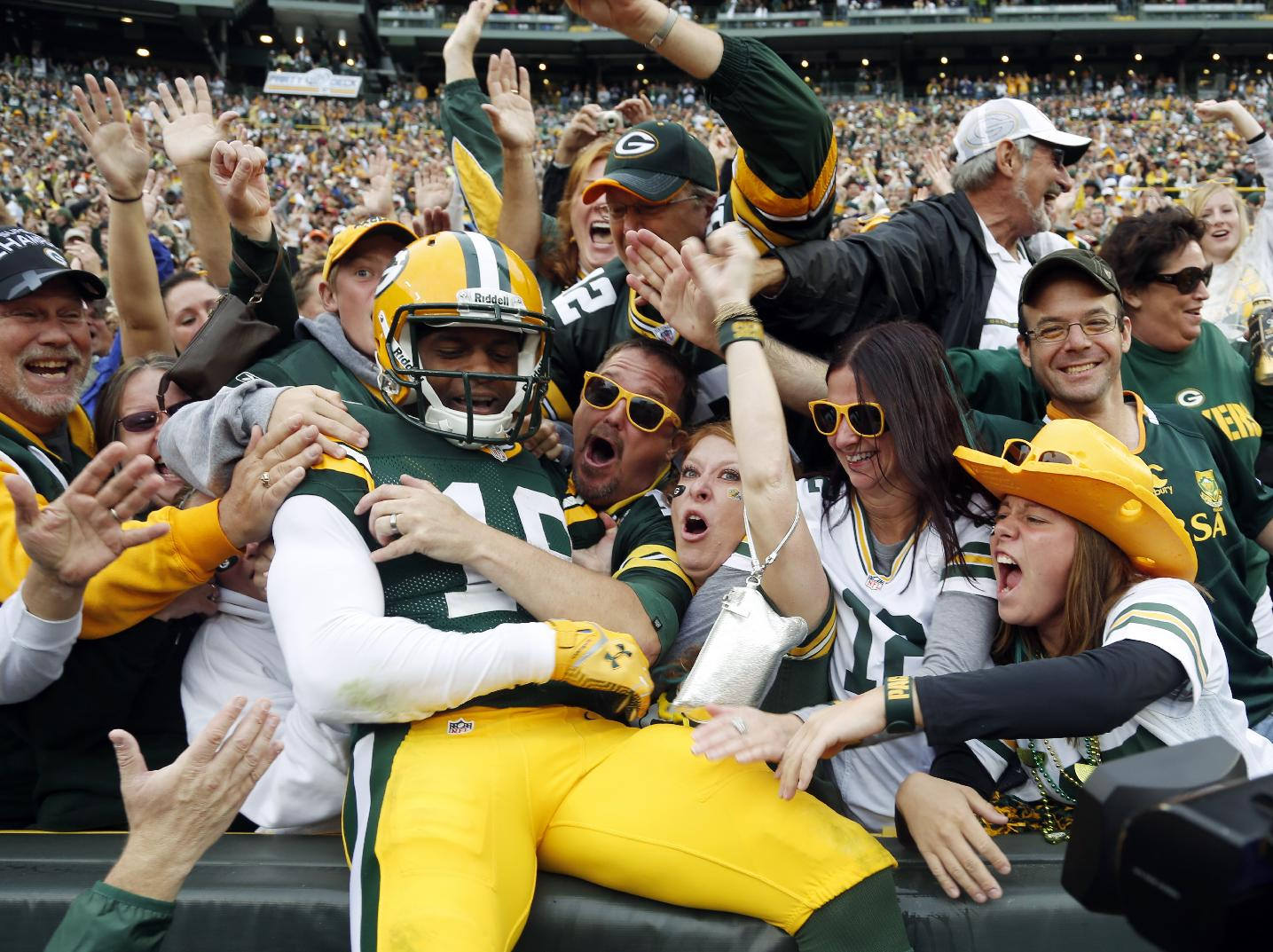 Green Bay Packers' Randall Cobb celebrates with fans after catching a touchdown pass during the first half of an NFL football game against the Washington Redskins Sunday, Sept. 15, 2013, in Green Bay, Wis