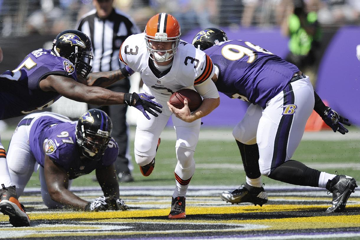 Cleveland Browns quarterback Brandon Weeden (3) scrambles between Baltimore Ravens outside linebacker Terrell Suggs, top left, defensive end Arthur Jones (97) and defensive end Marcus Spears, right, during the first half of an NFL football game in Baltimore, Md., Sunday, Sept. 15, 2013