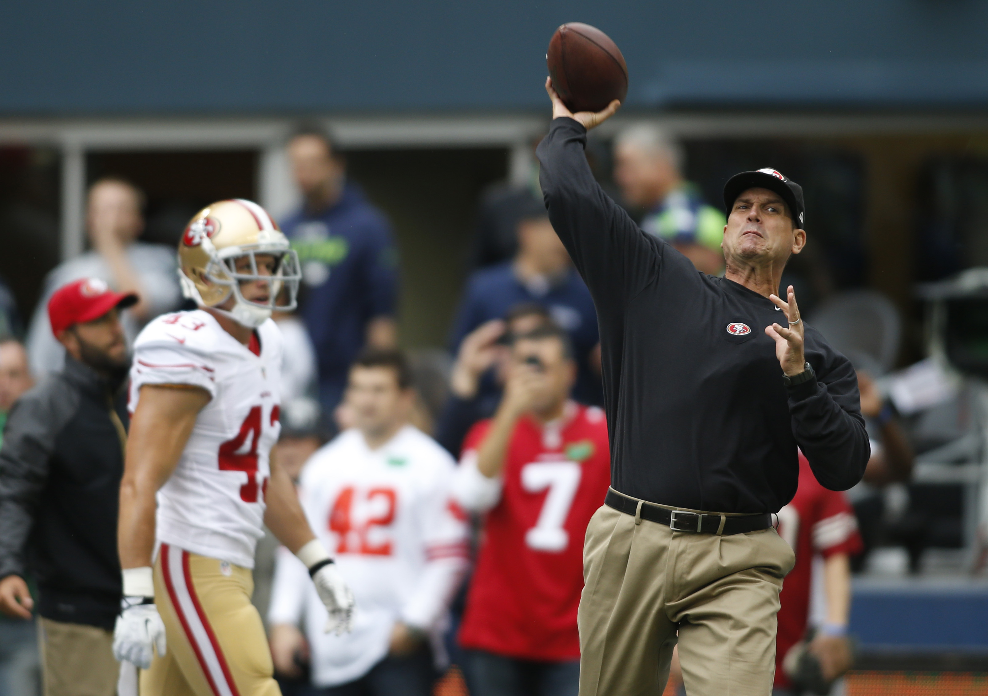 San Francisco 49ers head coach Jim Harbaugh, right, passes during warmups before an NFL football game against the Seattle Seahawks, Sunday, Sept. 15, 2013, in Seattle