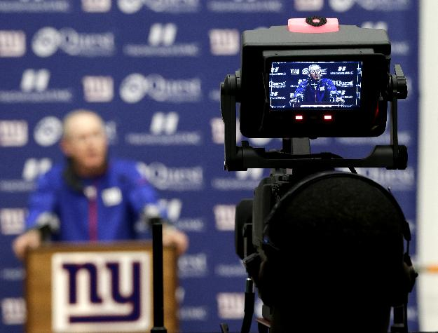 New York Giants head coach Tom Coughlin, displayed in the monitor of a video camera, talks to the media during an availability before the start of NFL football practice, Wednesday, Sept. 18, 2013, in East Rutherford, N.J. The Giants face the Carolina Panthers on Sunday, Sept. 22, in Charlotte
