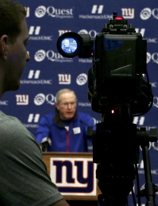 New York Giants head coach Tom Coughlin, displayed in the viewfinder of a video camera, talks to the media during an availabiliy before the start of NFL football practice, Wednesday, Sept. 18, 2013, in East Rutherford, N.J. The Giants face the Carolina Panthers on Sunday, Sept. 22, in Charlotte