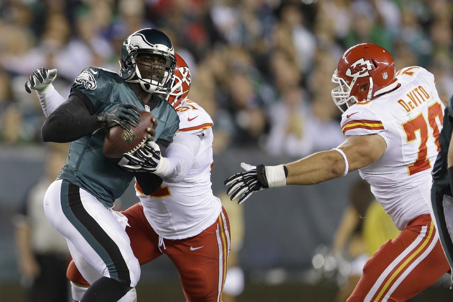 Philadelphia Eagles' Michael Vick, left, is cornered by Kansas City Chiefs' Tamba Hali and Mike DeVito during the first half of an NFL football game, Thursday, Sept. 19, 2013, in Philadelphia