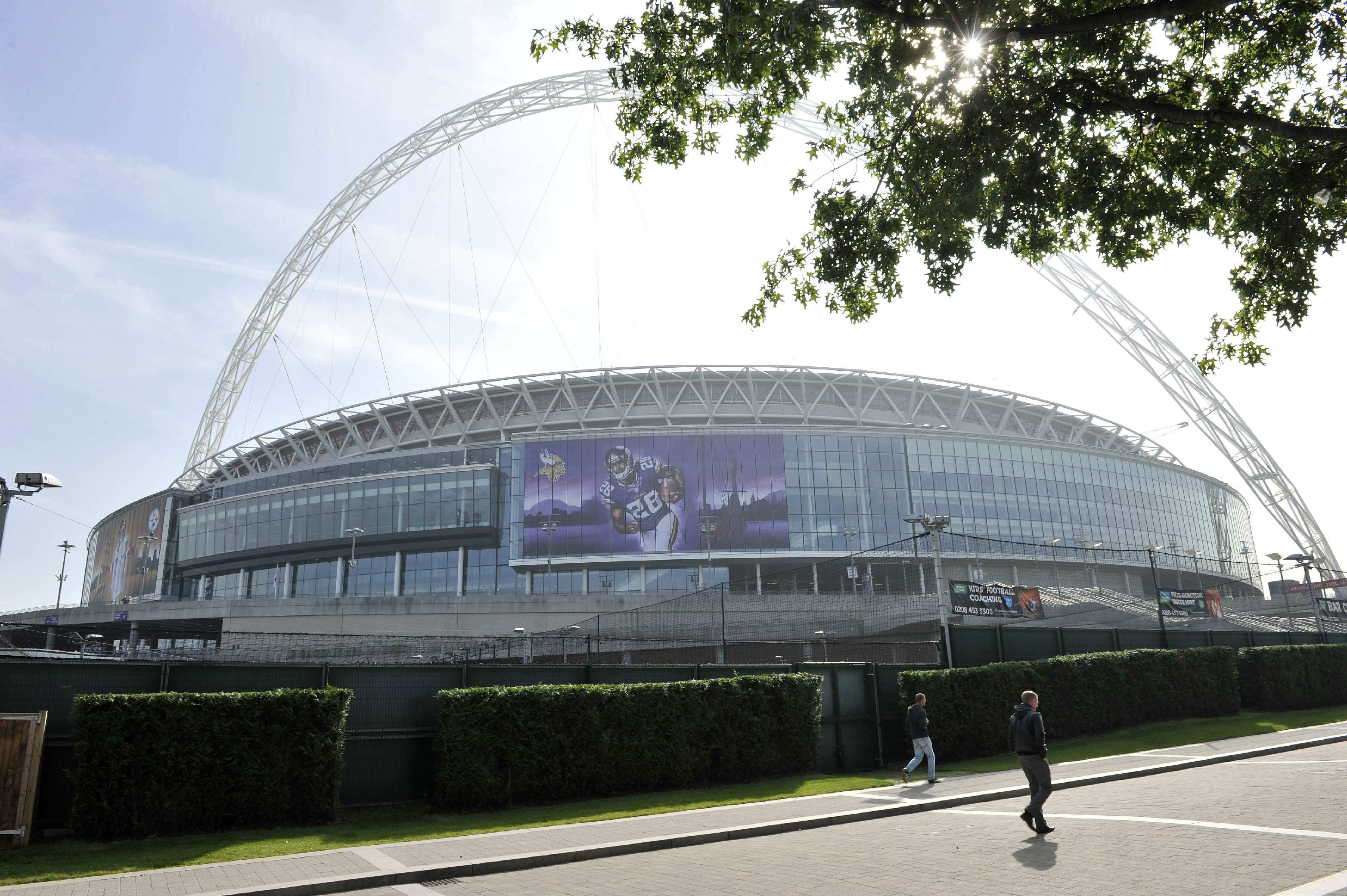 People walk past Wembley Stadium in London, Tuesday Sept. 24, 2013. The Pittsburgh Steelers are to play the Minnesota Vikings in the NFL International Series at Wembley Stadium in London on Sunday, Sept 29