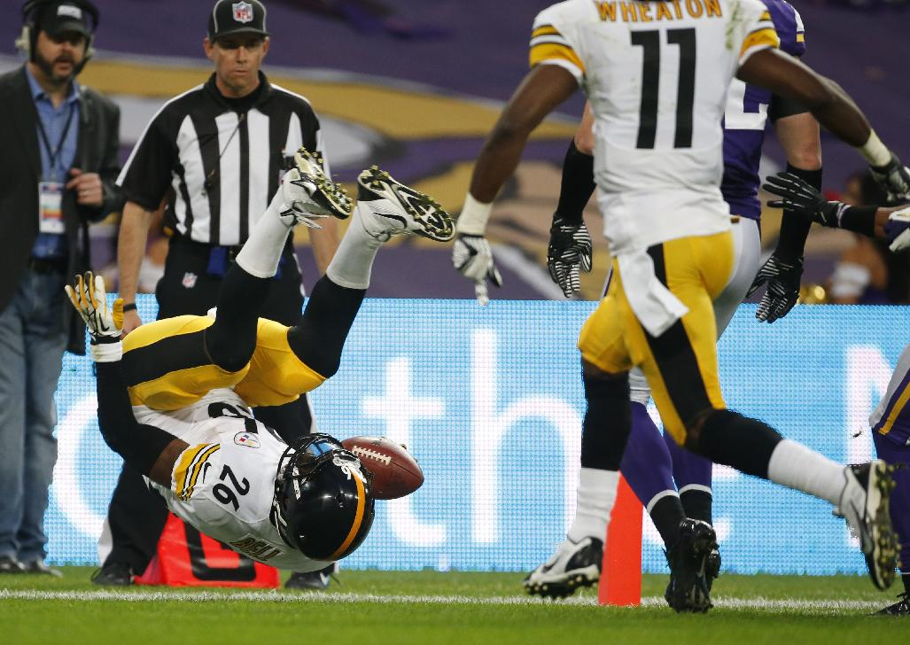 Pittsburgh Steelers running back Le'Veon Bell flips over as he scores on an eight-yard touchdown run during the NFL football game against Minnesota Vikings at Wembley Stadium, London, Sunday, Sept. 29, 2013