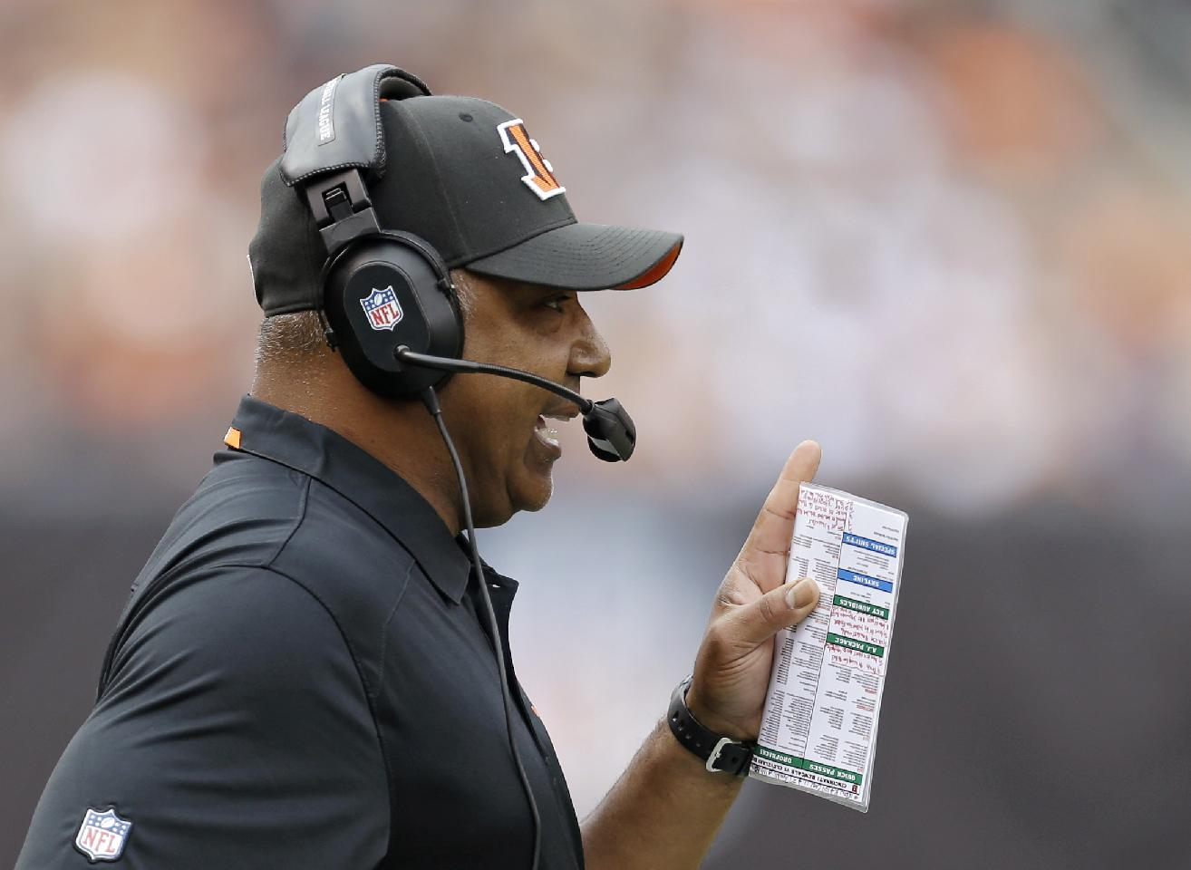 Cincinnati Bengals head coach Marvin Lewis talks on his headset in the first quarter of an NFL football game against the Cleveland Browns Sunday, Sept. 29, 2013, in Cleveland