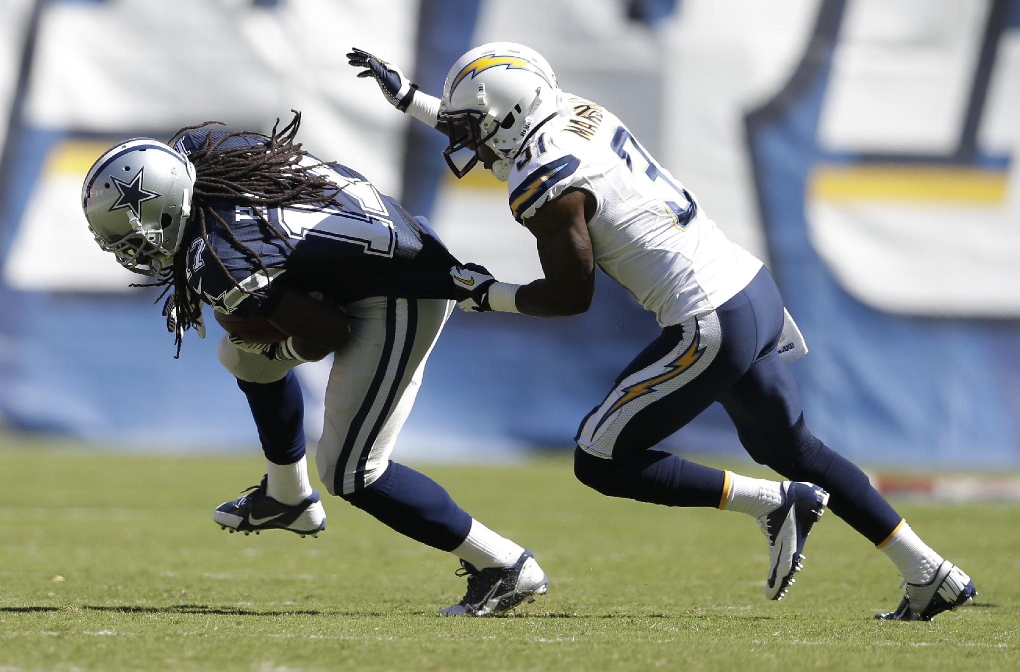San Diego Chargers linebacker Larry English grabs Dallas Cowboys wide receiver Dwayne Harris during the first half of an NFL football game Sunday, Sept. 29, 2013, in San Diego