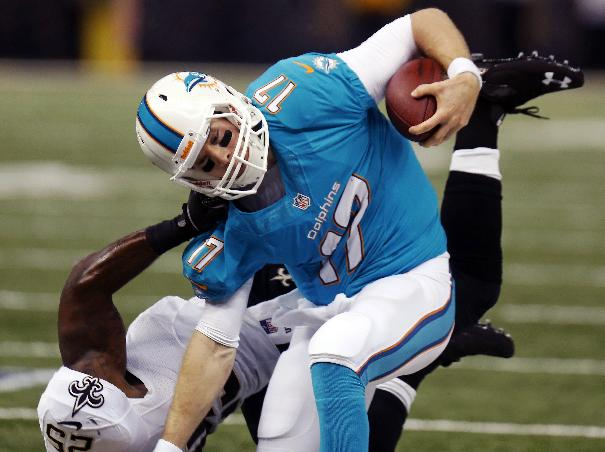 Miami Dolphins quarterback Ryan Tannehill (17) is dragged down by New Orleans Saints defensive back Rafael Bush (25) in the first half of an NFL football game in New Orleans, Monday, Sept. 30, 2013
