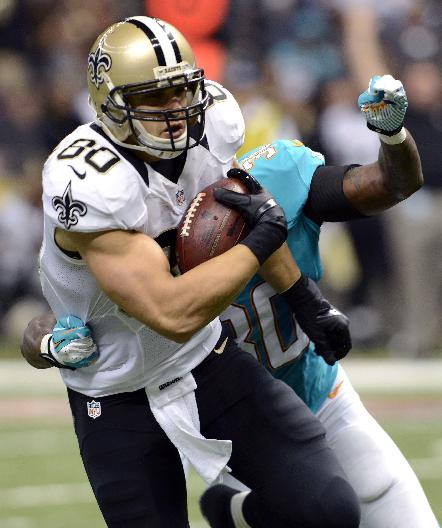 New Orleans Saints tight end Jimmy Graham (80) carries a touchdown reception as Miami Dolphins strong safety Chris Clemons (30) attempts the tackle in the second half of an NFL football game in New Orleans, Monday, Sept. 30, 2013