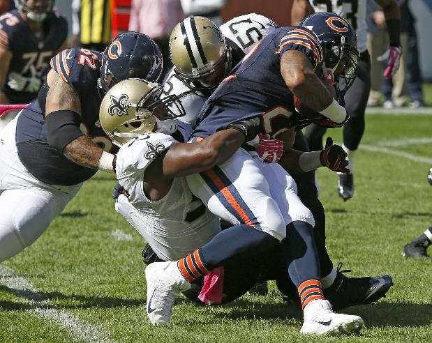New Orleans Saints linebackers Jay Richardson (56) and David Hawthorne (57) tackle Chicago Bears running back Matt Forte (22) during the first half of an NFL football game, Sunday, Oct. 6, 2013, in Chicago
