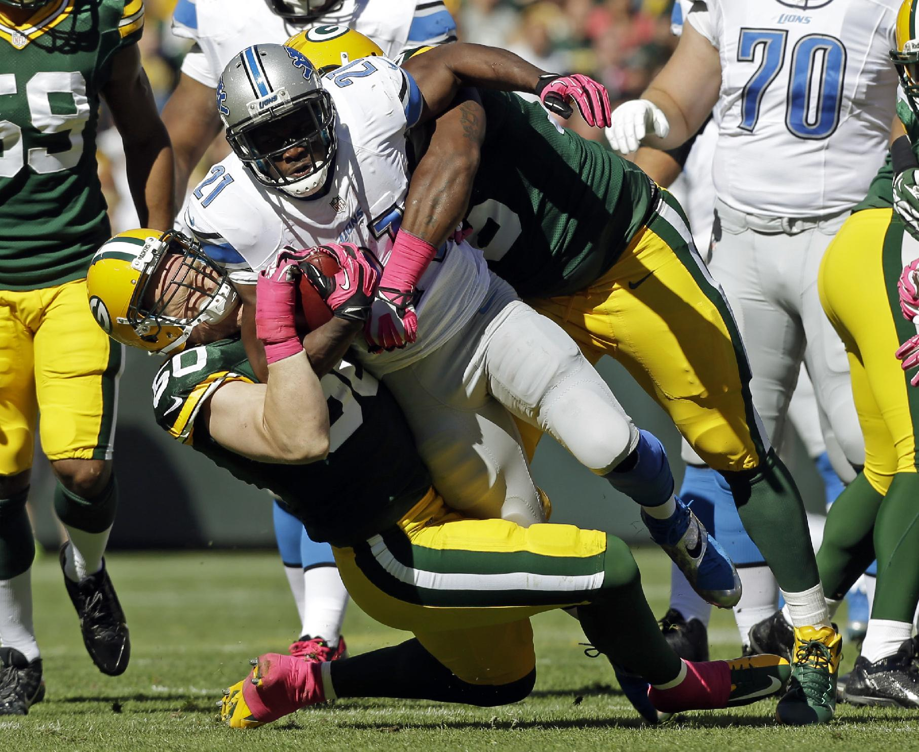 Green Bay Packers' Mike Daniels and A.J. Hawk (50) tackle Detroit Lions' Reggie Bush (21) during the first half of an NFL football game Sunday, Oct. 6, 2013, in Green Bay, Wis