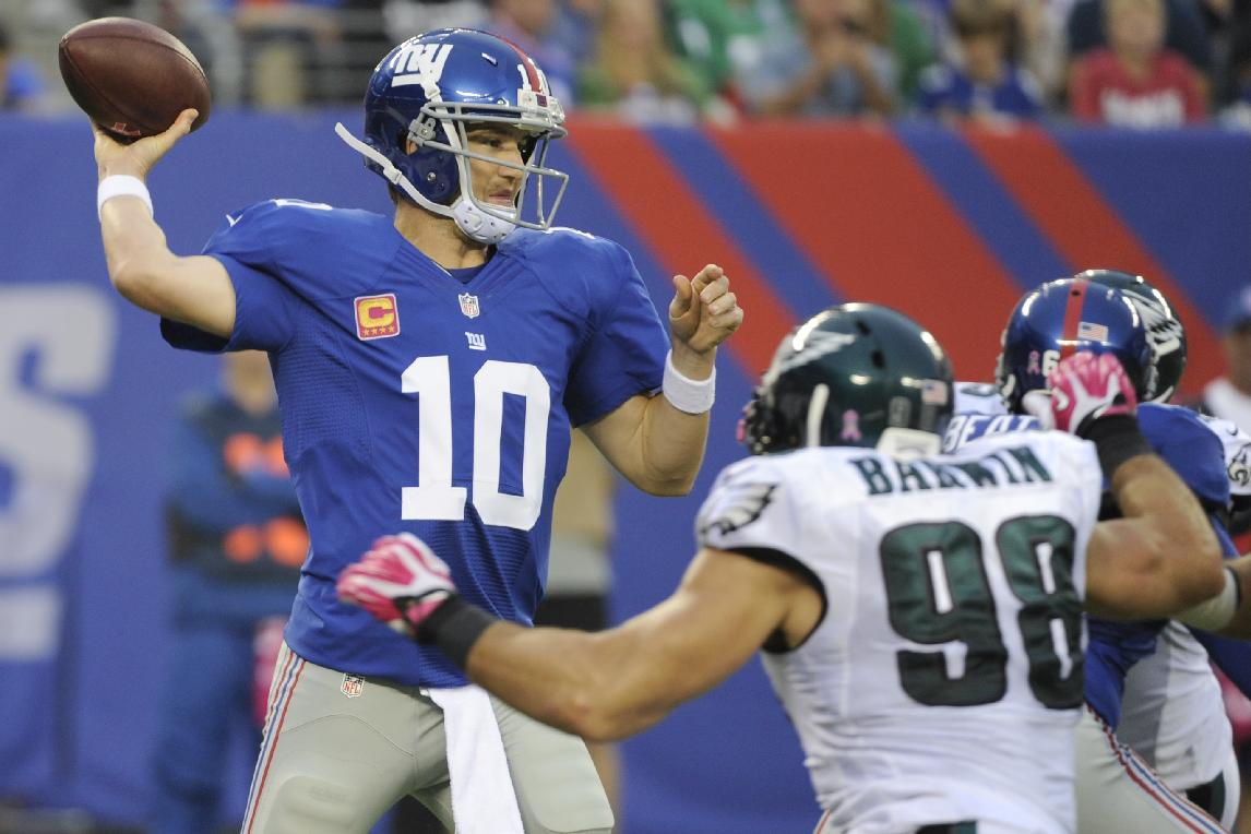 New York Giants' Eli Manning (10) throws a pass as Philadelphia Eagles' Connor Barwin (98) rushes during the first half of an NFL football game on Sunday, Oct. 6, 2013, in East Rutherford, N.J