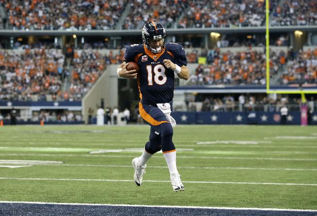 Denver Broncos quarterback Peyton Manning (18) sprints to the end zone untouched for a touchdown on a quarterback keep play in the first half of an NFL football game against the Dallas Cowboys, Sunday, Oct. 6,2013, in Arlington, Texas