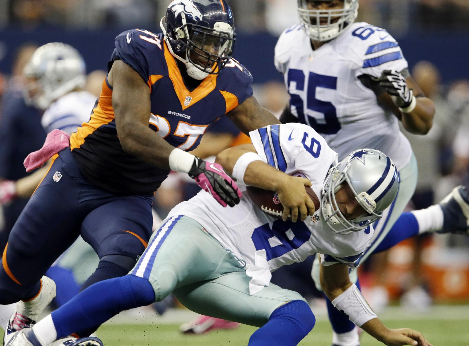 Denver Broncos defensive end Malik Jackson, left, takes down Dallas Cowboys quarterback Tony Romo (9) during the second quarter of an NFL football game Sunday, Oct. 6, 2013, in Arlington, Texas