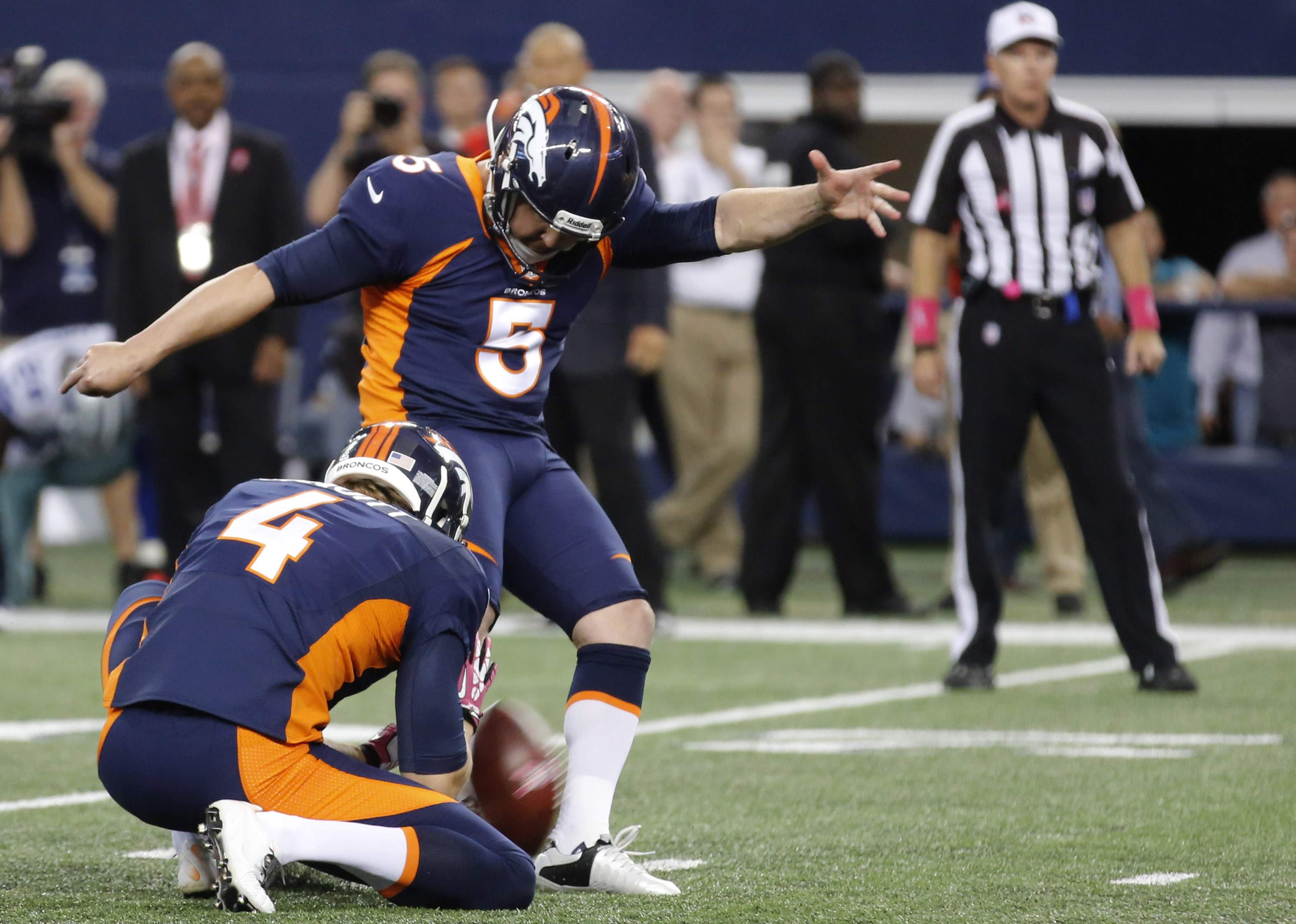 With Denver Broncos' Britton Colquitt (4) holding kicker Matt Prater (5) kicks the game-winning field goal against the Dallas Cowboys during the fourth quarter of an NFL football game Sunday, Oct. 6,2013, in Arlington, Texas. The Broncos won 51-48