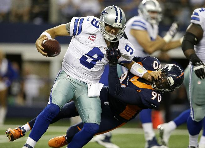 Dallas Cowboys quarterback Tony Romo (9) attempts to fight off a sack by Denver Broncos' Shaun Phillips (90) late in the fourth quarter of an NFL football game Sunday, Oct. 6,2013, in Arlington, Texas. The Broncos won 51-48