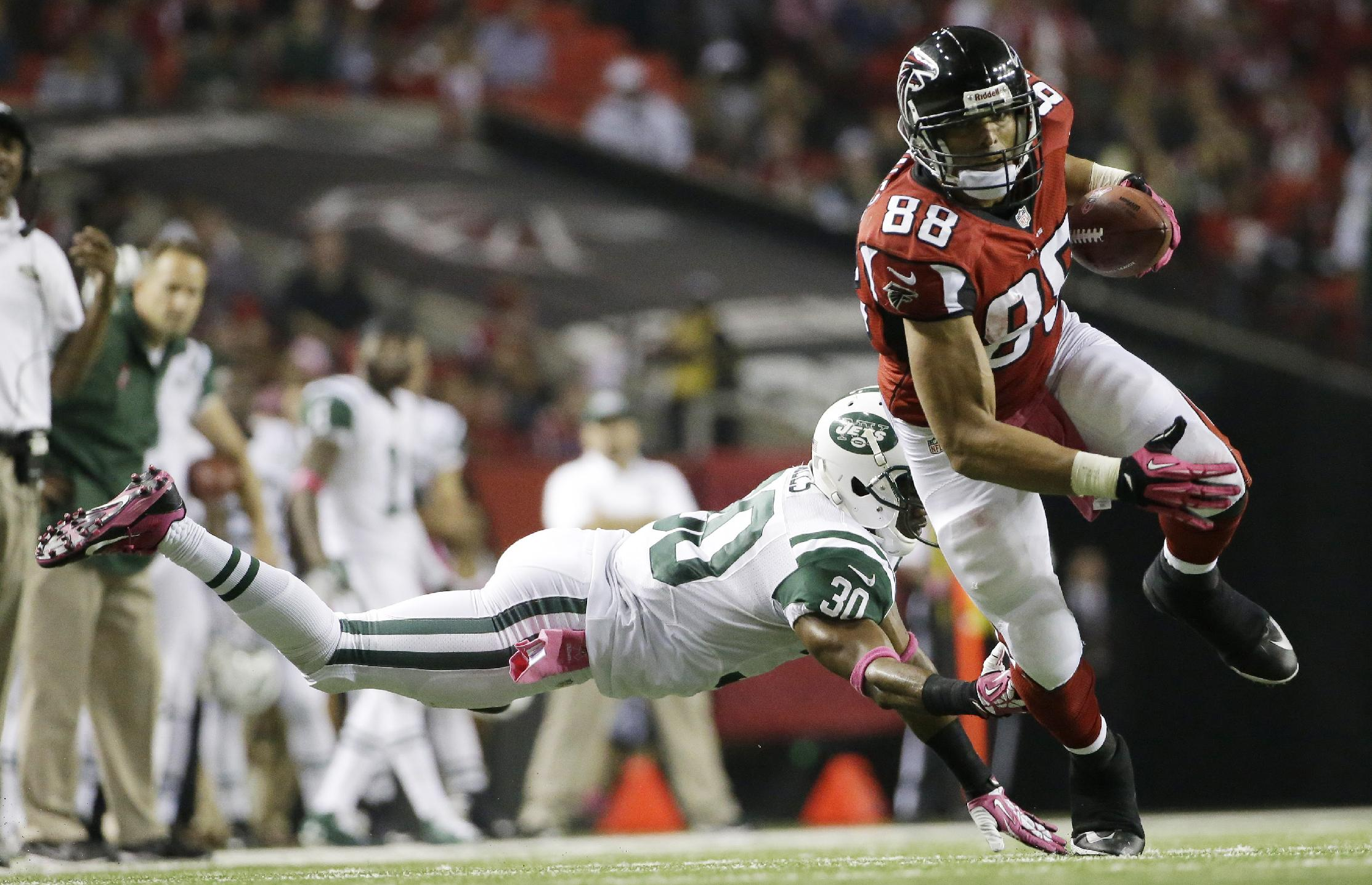 Atlanta Falcons tight end Tony Gonzalez (88) moves the ball after a catch as New York Jets cornerback Darrin Walls (30) defends during the second half of an NFL football game, Monday, Oct. 7, 2013, in Atlanta