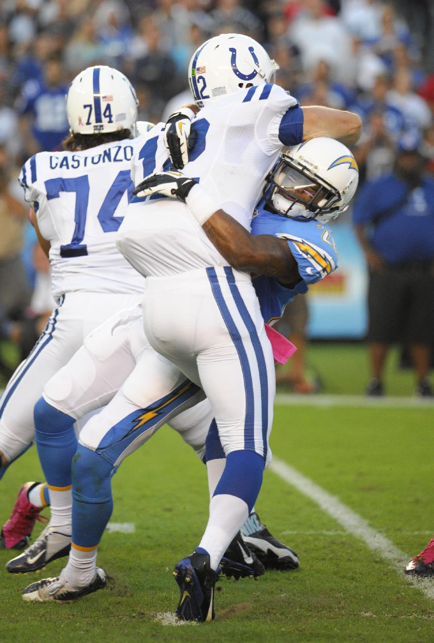 San Diego Chargers cornerback Johnny Patrick, right, hits Indianapolis Colts quarterback Andrew Luck, center, as he releases a pass during the first half of an NFL football game Monday, Oct. 14, 2013, in San Diego