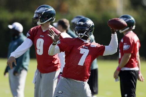 Philadelphia Eagles quarterback Michael Vick, right, and Nick Foles throw passes during practice at the NFL football team's training facility, Tuesday, Oct. 15, 2013, in Philadelphia