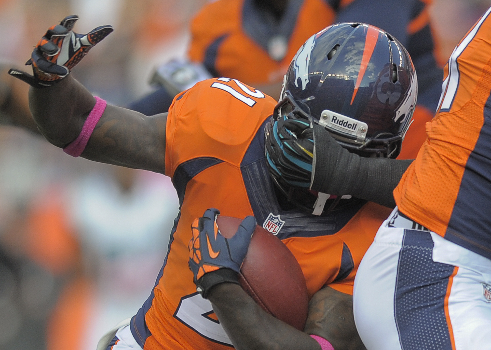 CORRECTS ID TO RONNIE HILLMAN, NOT KNOWSHON MORENO - Denver Broncos running back Ronnie Hillman (21) has his face mask grabbed as he runs the ball against the Jacksonville Jaguars in the third quarter of an NFL football game, Sunday, Oct. 13, 2013, in Denver