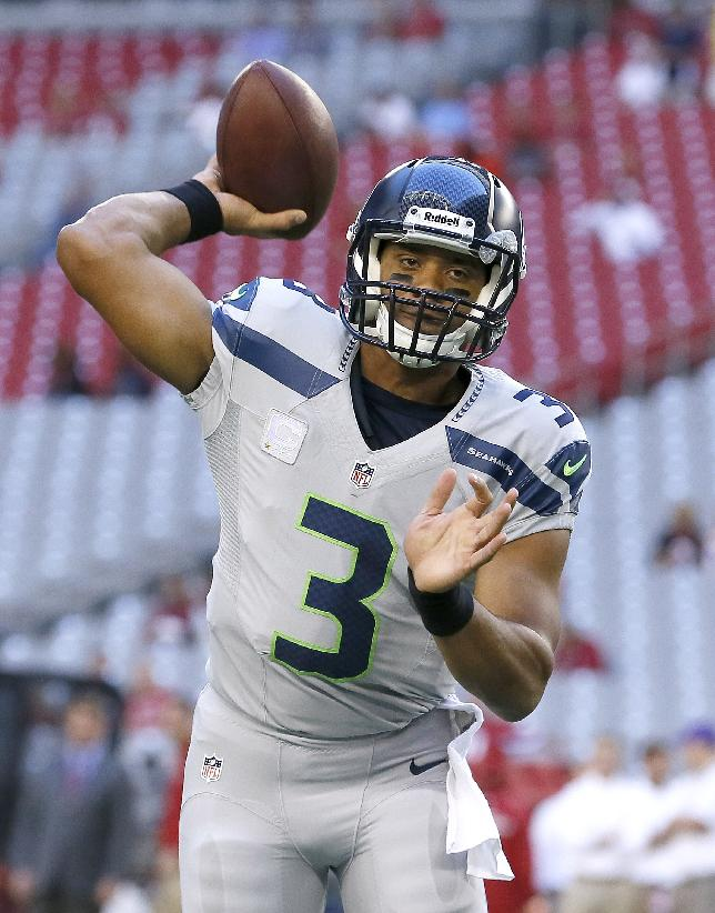 Seattle Seahawks quarterback Russell Wilson warms up for an NFL football game against the Arizona Cardinals, Thursday, Oct. 17, 2013, in Glendale, Ariz