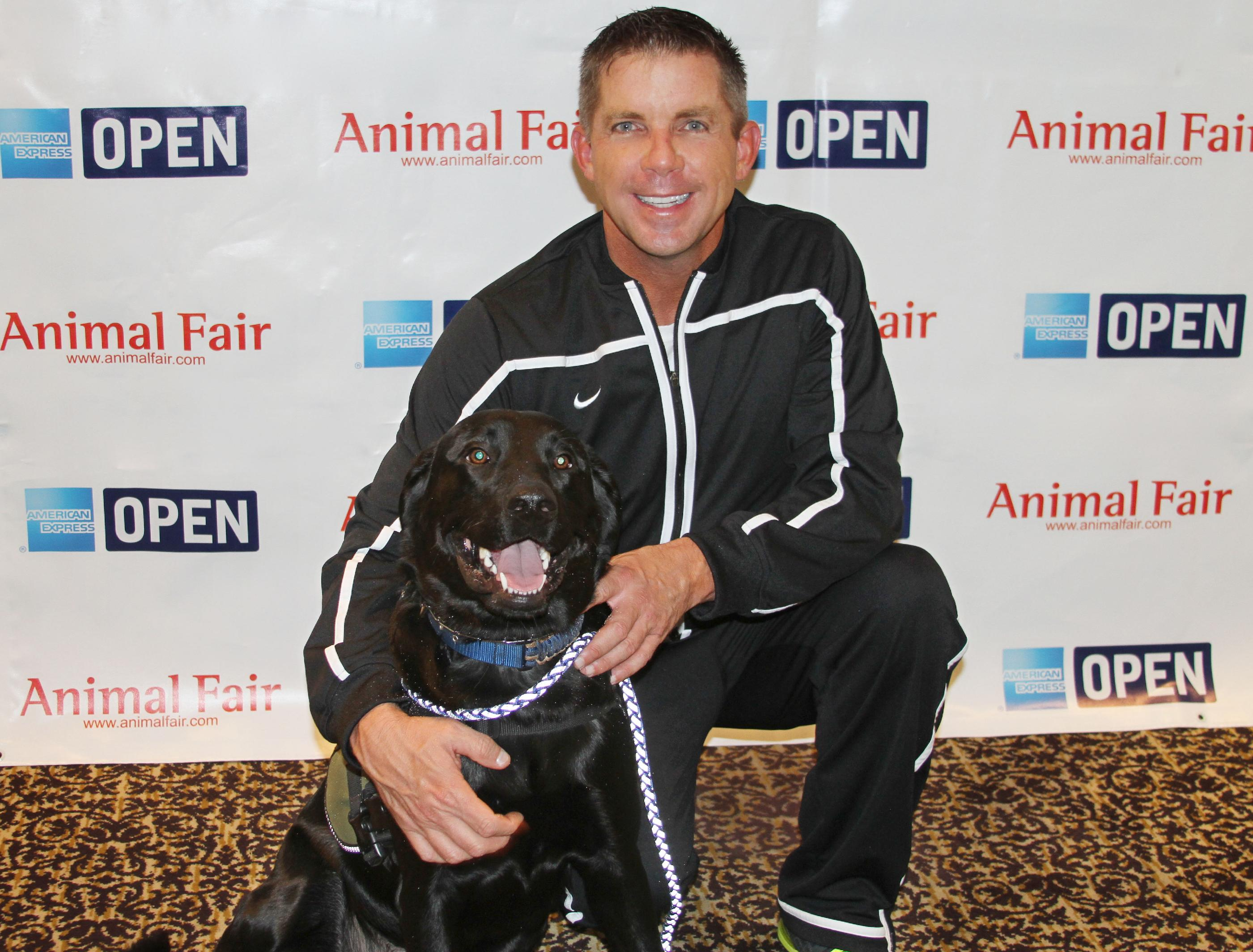 In this photo provided by Animal Fair Media, Inc., New Orleans Saints Coach Sean Payton poses with Service Dog Seal at the