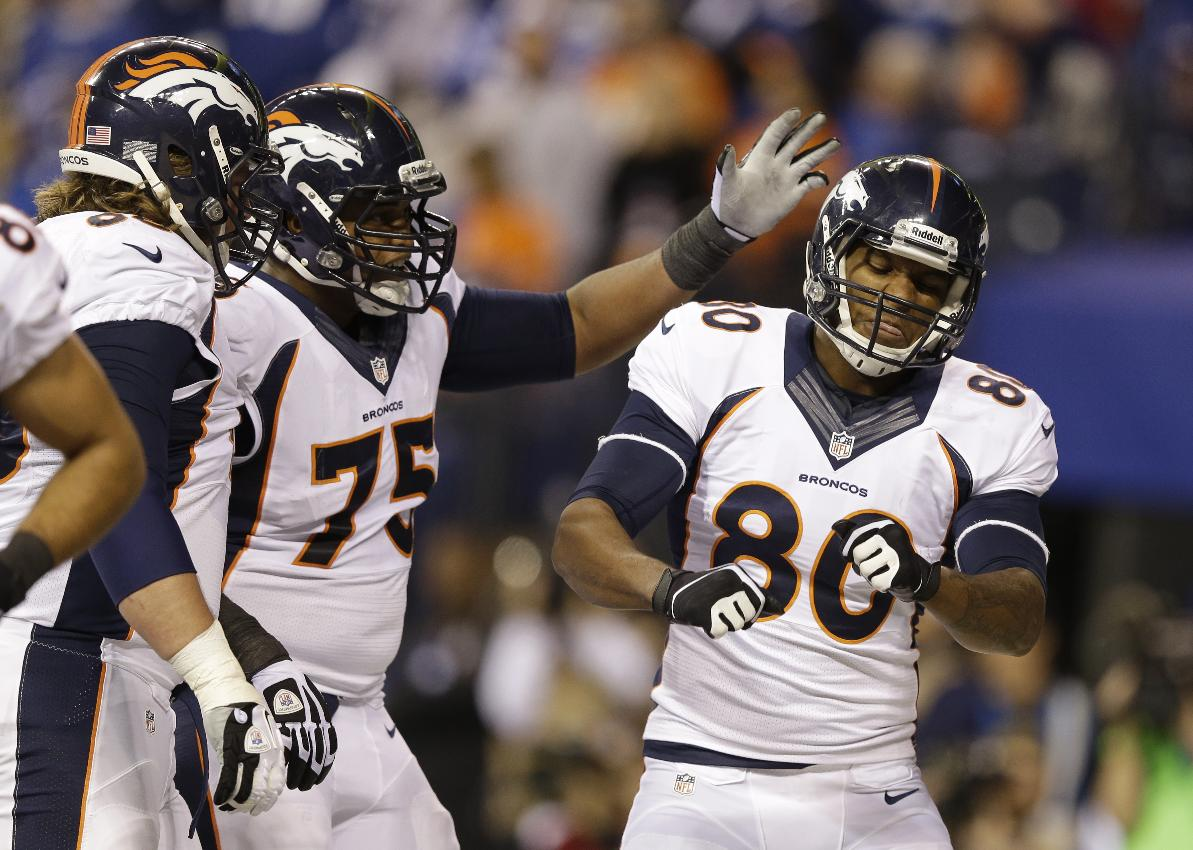 Denver Broncos' Julius Thomas (80) celebrates his touchdown in the end zone with Chris Clark (75) and Zane Beadles during the first half of an NFL football game, Sunday, Oct. 20, 2013, in Indianapolis
