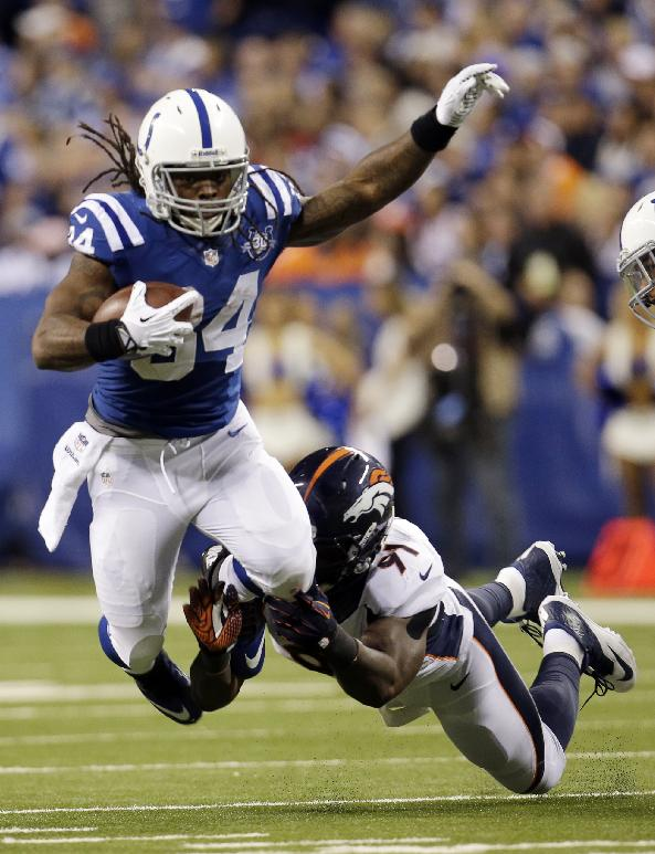 Indianapolis Colts running back Trent Richardson (34) is tripped up by Denver Broncos defensive end Robert Ayers (91) during the first half of an NFL football game, Sunday, Oct. 20, 2013, in Indianapolis
