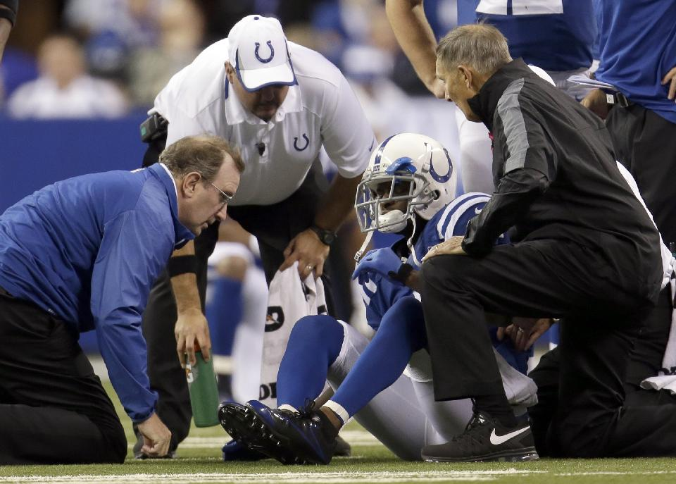 Trainers talk to Indianapolis Colts wide receiver Reggie Wayne (87) after Wayne injures his knee during the second half of an NFL football game, Sunday, Oct. 20, 2013, in Indianapolis