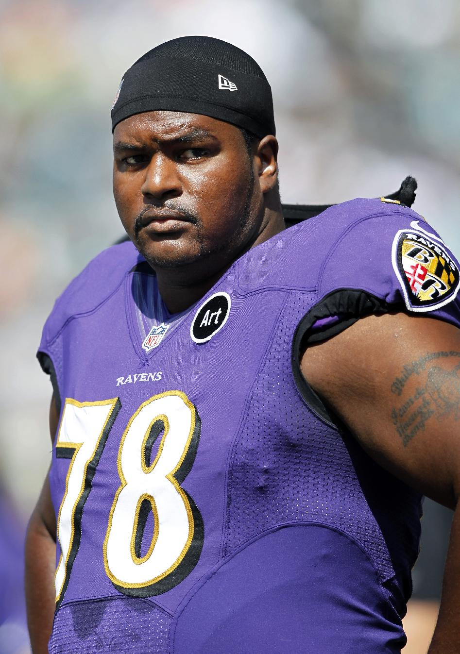 In this Sept. 16, 2012, file photo, Baltimore Ravens tackle Bryant McKinnie stands on the field before an NFL football game against the Philadelphia Eagles, in Philadelphia. McKinnie has been traded by the Ravens to the Miami Dolphins, who are anxious to shore up a leaky offensive line. The Ravens will receive a conditional late-round draft pick, coach John Harbaugh said Monday, Oct. 21, 2013