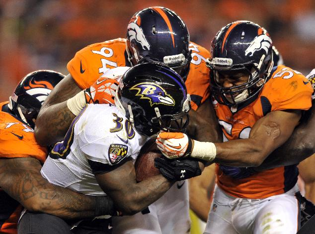 In this Sept. 25, 2013 file photo, Baltimore Ravens running back Bernard Pierce (30) is gang tackled by Denver Broncos defensive tackle Kevin Vickerson (99) , Terrance Knighton (94) and Wesley Woodyard (52) during an NFL football game, in Denver. Increasingly, teams are having trouble getting what they need on the ground on third or fourth down, with 2 or fewer yards needed for a first down or a touchdown. And increasingly, they're trying to pass for those short gains