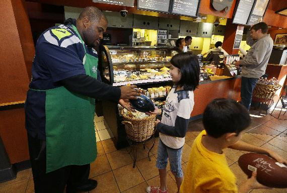 Seattle Seahawks NFL football defensive tackle Brandon Mebane, left, signs footballs for young fans Myhanh Wong, 11, center, and Myhanh's brother Tai Wong, 7, right, at a Seattle Starbucks store on Wednesday, Oct. 23, 2013, in Seattle. The Seahawks began a one-week fund-raising campaign Wednesday with Starbucks to benefit Seahawks head coach Pete Carroll's A Better Seattle program, which seeks to reach at-risk youth and prevent gang violence