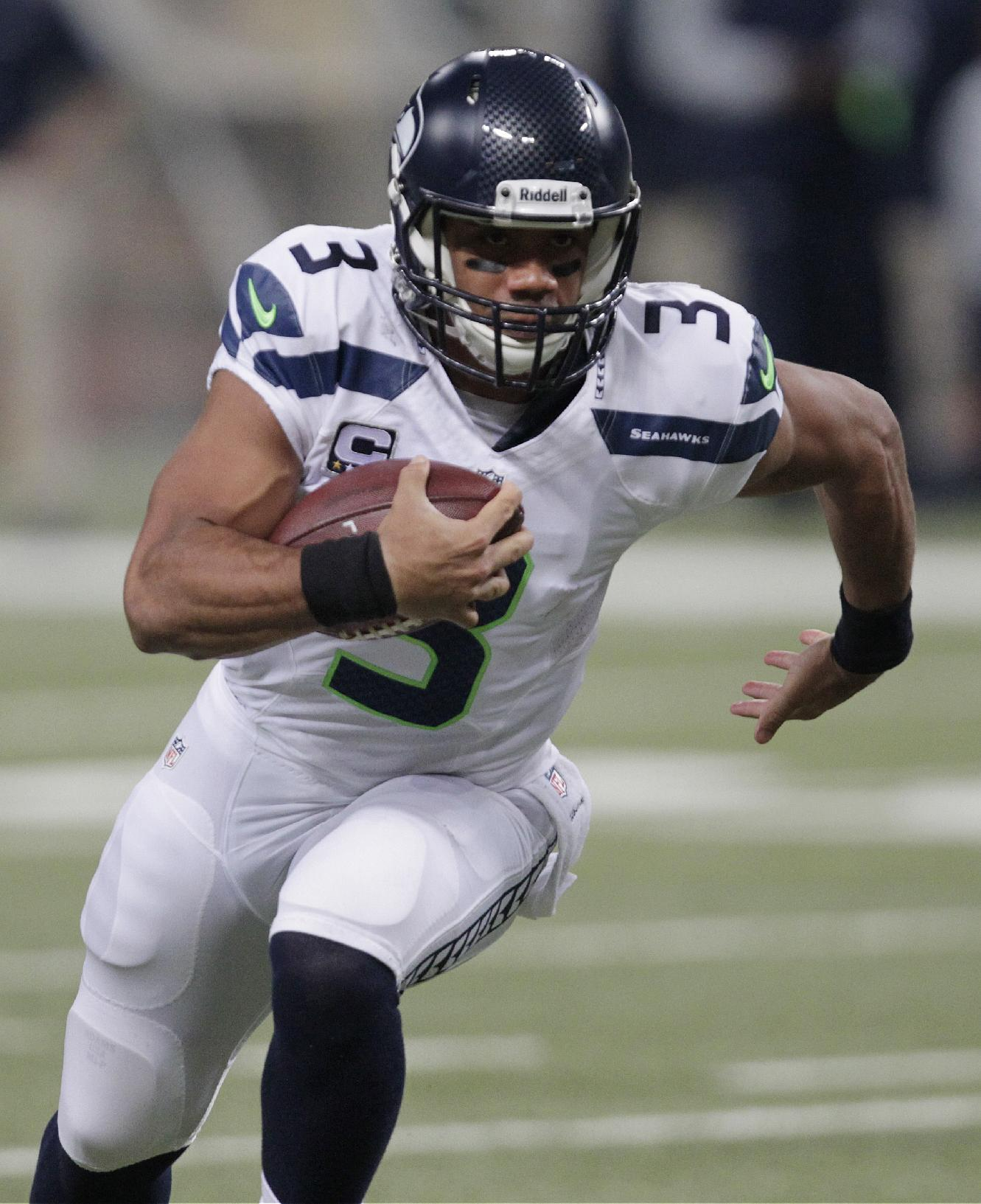 Seattle Seahawks quarterback Russell Wilson (3) rushes against the St. Louis Rams defense during the first half of an NFL football game, Monday, Oct. 28, 2013, in St. Louis