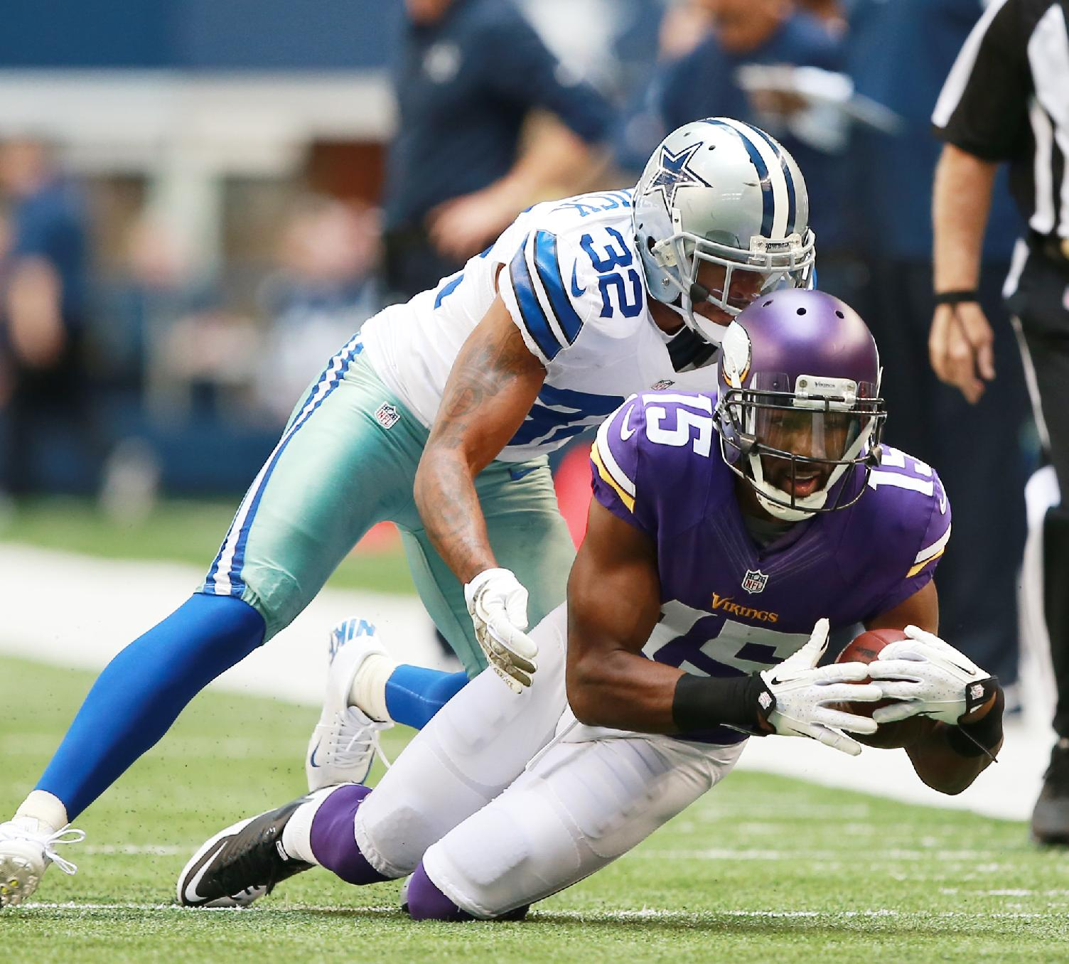 Minnesota Vikings wide receiver Greg Jennings (15) is tackled by Dallas Cowboys cornerback Orlando Scandrick (32) during the first half of an NFL football game Sunday, Nov. 3, 2013, in Arlington, Texas