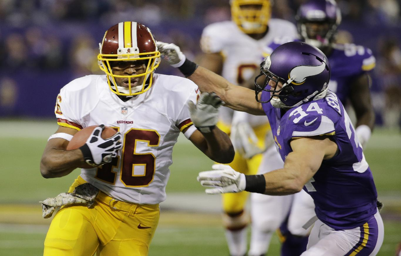 Washington Redskins running back Alfred Morris, left, runs from Minnesota Vikings strong safety Andrew Sendejo during the first half of an NFL football game Thursday, Nov. 7, 2013, in Minneapolis