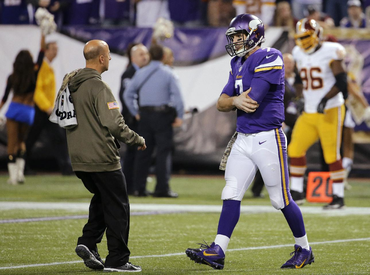 Minnesota Vikings quarterback Christian Ponder, right, is attended to by a trainer after an injury to his left shoulder during the second half of an NFL football game against the Washington Redskins, Thursday, Nov. 7, 2013, in Minneapolis