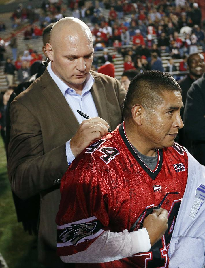 Former New Mexico and Chicago Bears football player Brian Urlacher, left, signs Marvin Lamy's Urlacher jersey prior to Urlacher's jersey number retired during a halftime ceremony at an NCAA college football game against the Air Force on Friday, Nov. 8, 2013, in Albuquerque, N.M