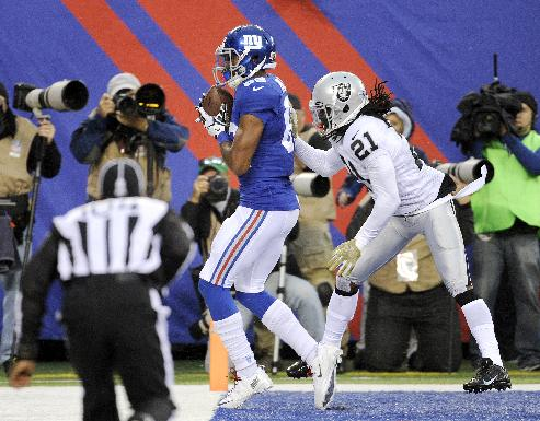 New York Giants wide receiver Rueben Randle keeps his feet in bounds as he catches a touchdown pass as Oakland Raiders cornerback Mike Jenkins (21) defends on the play during the first half of an NFL football game, Sunday, Nov. 10, 2013, in East Rutherford, N.J