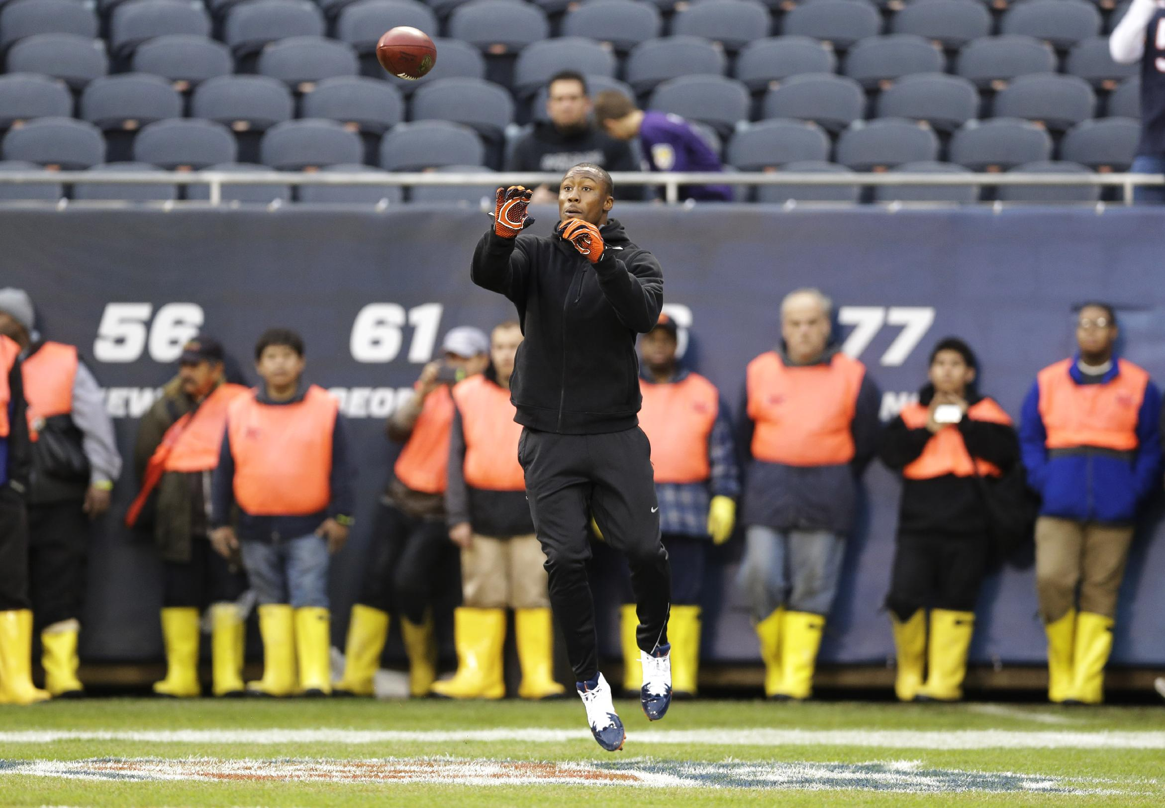 Chicago Bears wide receiver Brandon Marshall warms up as members of the grounds crew line up against the wall before an NFL football game against the Baltimore Ravens, Sunday, Nov. 17, 2013, in Chicago