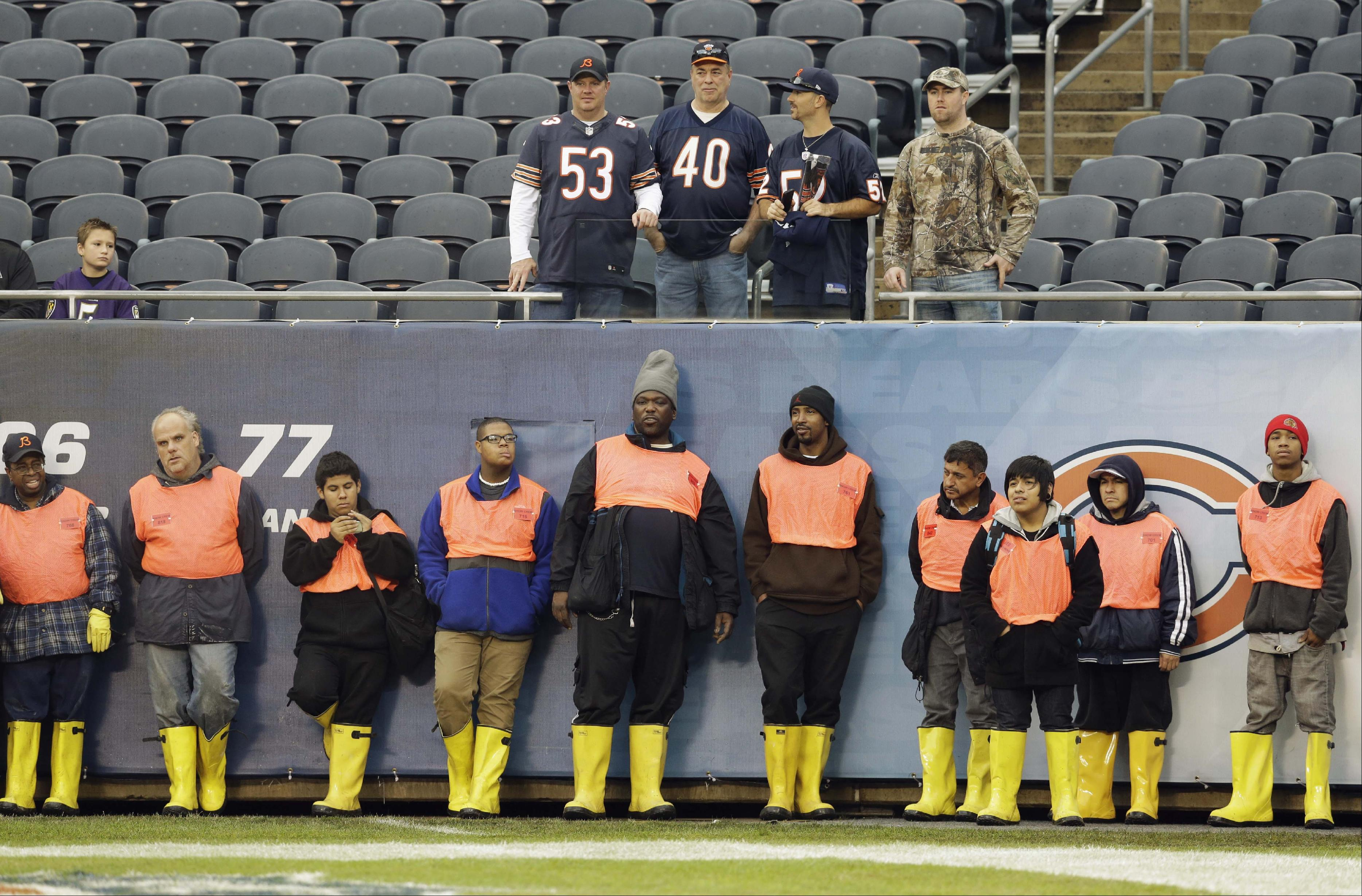 Soldier Field groundskeepers line up against the wall and a few Chicago Bears fans watch as players warm up before an NFL football against the Baltimore Ravens, Sunday, Nov. 17, 2013, in Chicago