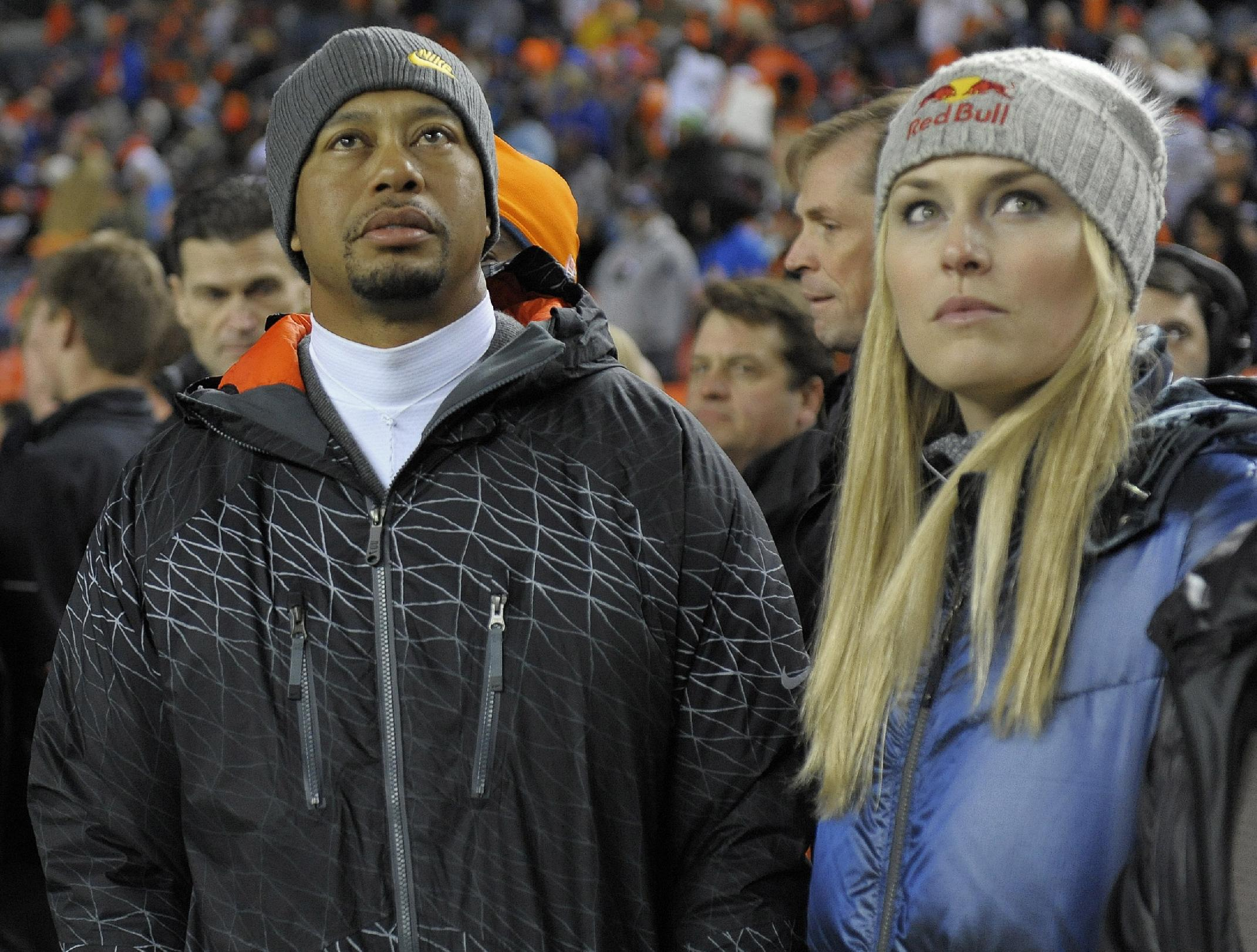 Tiger Woods, left, and Lindsey Vonn watch from the sidelines as the Denver Broncos and the Kansas City Chiefs warm up before an NFL football game, Sunday, Nov. 17, 2013, in Denver