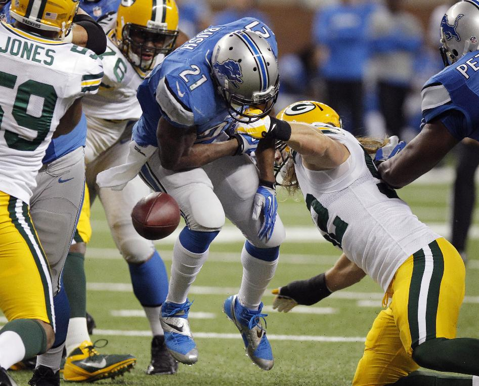 Detroit Lions running back Reggie Bush (21) fumbles during the first quarter of an NFL football game against the Green Bay Packers at Ford Field in Detroit, Thursday, Nov. 28, 2013