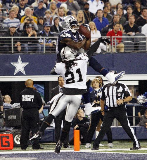 Dallas Cowboys wide receiver Dez Bryant, top, pulls in a touchdown, defending Oakland Raiders cornerback Mike Jenkins (21) during the second half of an NFL football game Thursday, Nov. 28, 2013, in Arlington, Texas