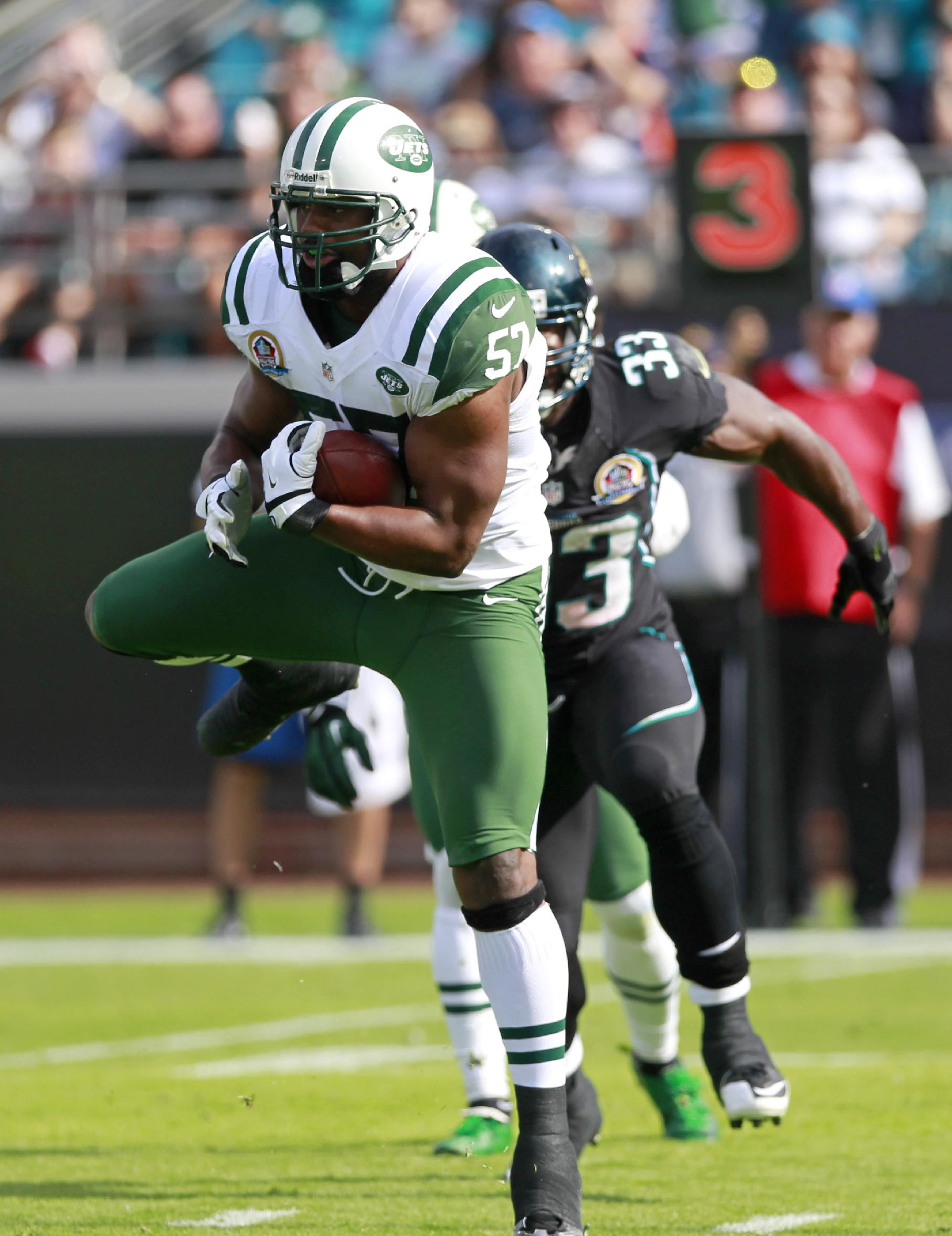 In this Dec. 9, 2012, file photo, New York Jets inside linebacker Bart Scott, left, intercepts a pass in front of Jacksonville Jaguars fullback Greg B. Jones (33) during the first half of an NFL football game in Jacksonville, Fla. Scott has made a seamless transition from the football field to the TV studio as one of the four hosts of CBS Sports Network's