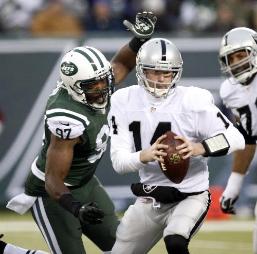 New York Jets outside linebacker Calvin Pace (97) closes in moments before sacking Oakland Raiders quarterback Matt McGloin (14) during the second half of an NFL football game, Sunday, Dec. 8, 2013, in East Rutherford, N.J. The Jets won 37-27